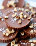 Close up of the Nutella fat bombs on a plate, topped with flakey salt and chopped hazelnuts.
