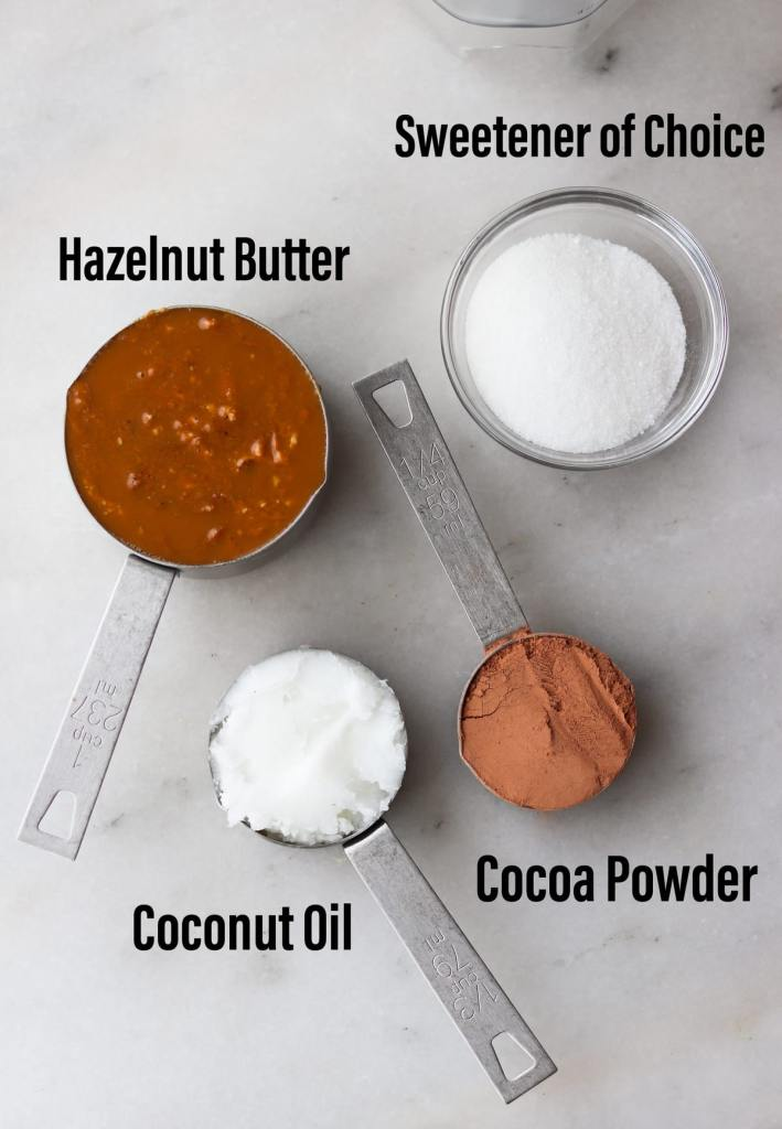 Top down of the recipe ingredients laid out on a marble board, labeled: hazelnut butter, sweetener, coconut oil, and cocoa powder.