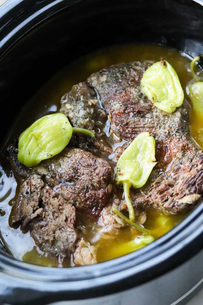 Close of up of the cooked beef and pepperoncini inside the slow cooker.