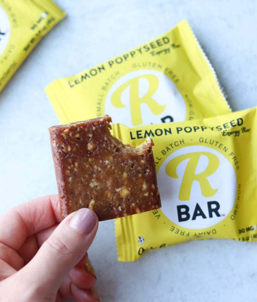 A hand holding a lemon poppyseed bar with a bite taken out of it beside the wrapper.