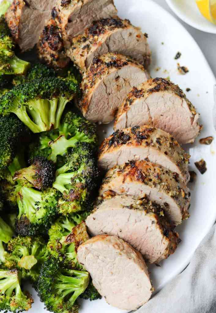The cooked, sliced and plated pork tenderloin on a white plate, served with roasted broccoli.