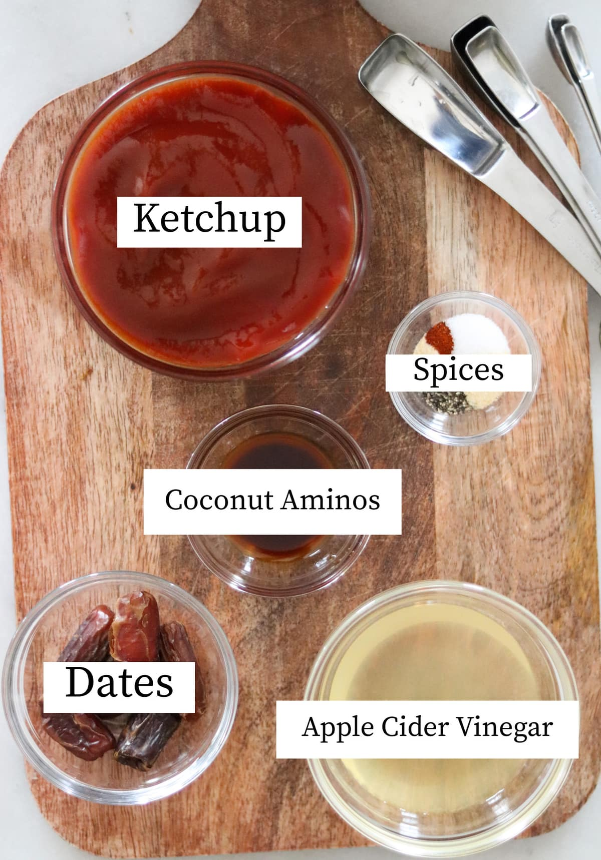 Recipe ingredients in small dishes laid out on a wooden cutting board and labeled: ketchup, spices, coconut aminos, dates, and apple cider vinegar.