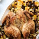 Top down of the finished oven roasted butterfly chicken and vegetables with the title in large print for Pinterest.