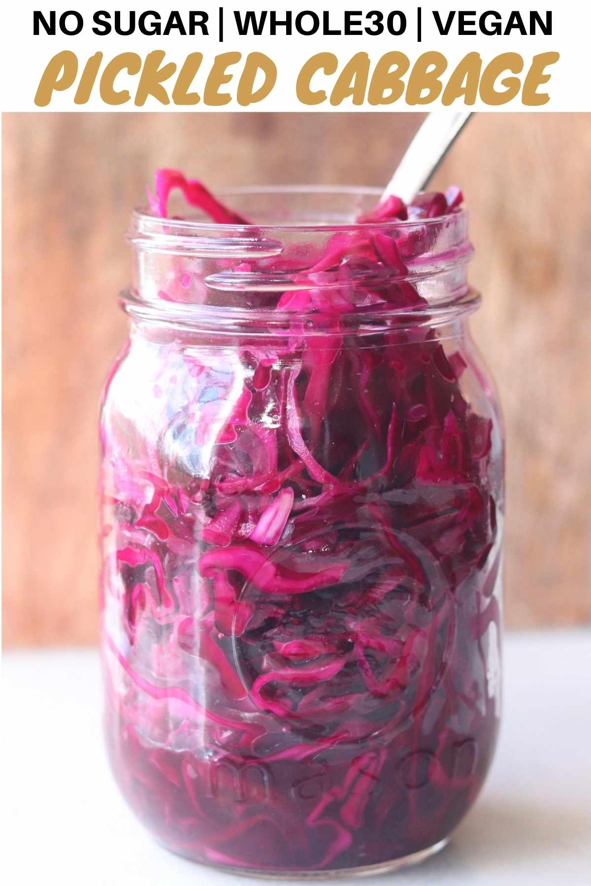 "Side view of a mason jar filled with purple cabbage with the words ""No sugar, Whole30, vegan pickled cabbage"" for Pinterest."