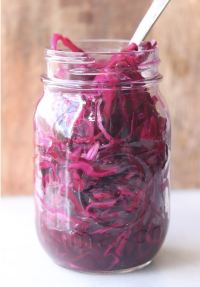 Side view of a mason jar filled with pickled red cabbage.