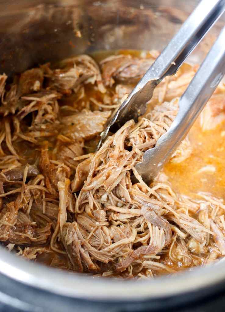 Close up of metal tongs taking the shredded pork out of the instant pot.