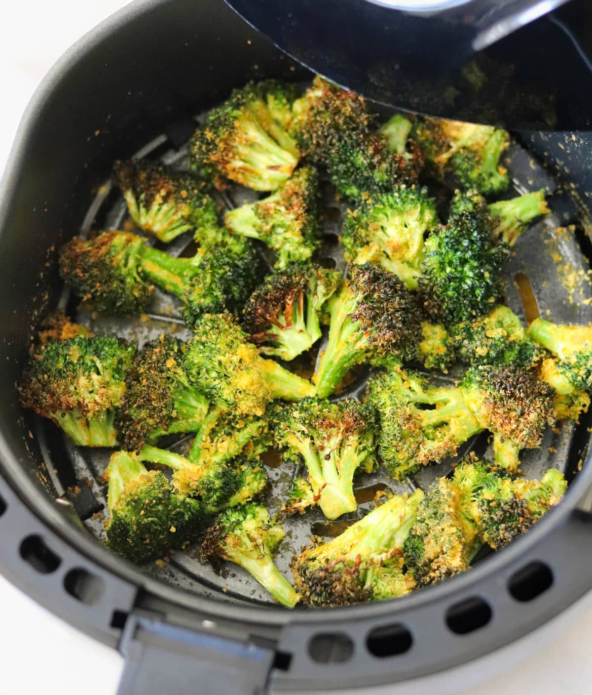 The finished crispy broccoli in the air fryer basket.