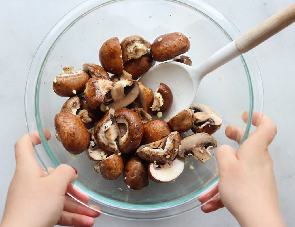 Two hands holding a glass bowl filled with sliced mushrooms tossed with oil and garlic.