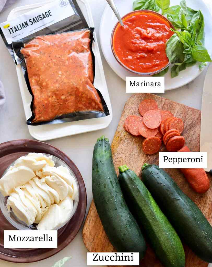 The recipe ingredients laid out on a white board and labeled: Italian sausage, marinara, mozzarella, pepperoni, and zucchini.