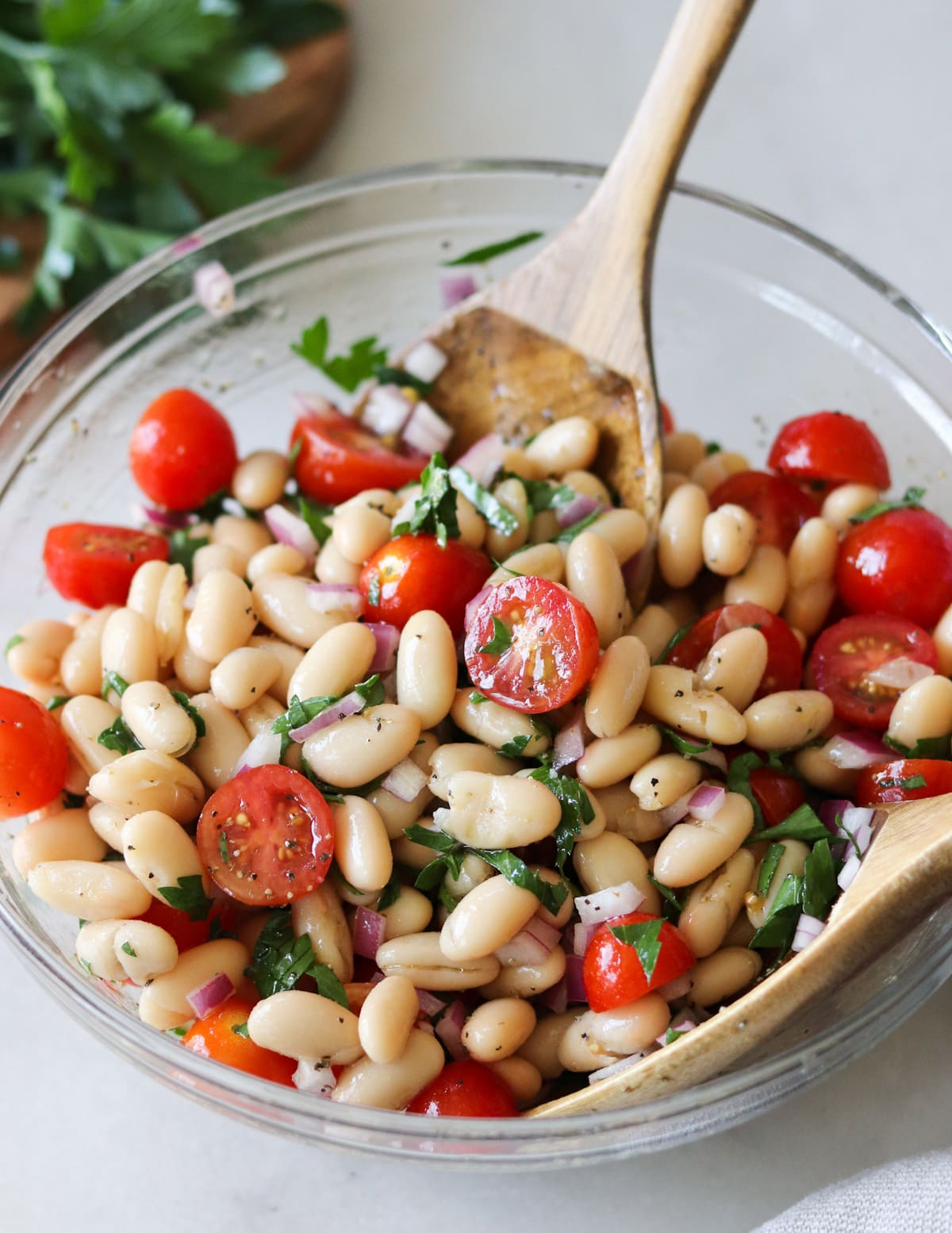 Close up side view of the finished Cannellini bean salad in a glass bowl with serving spoons.