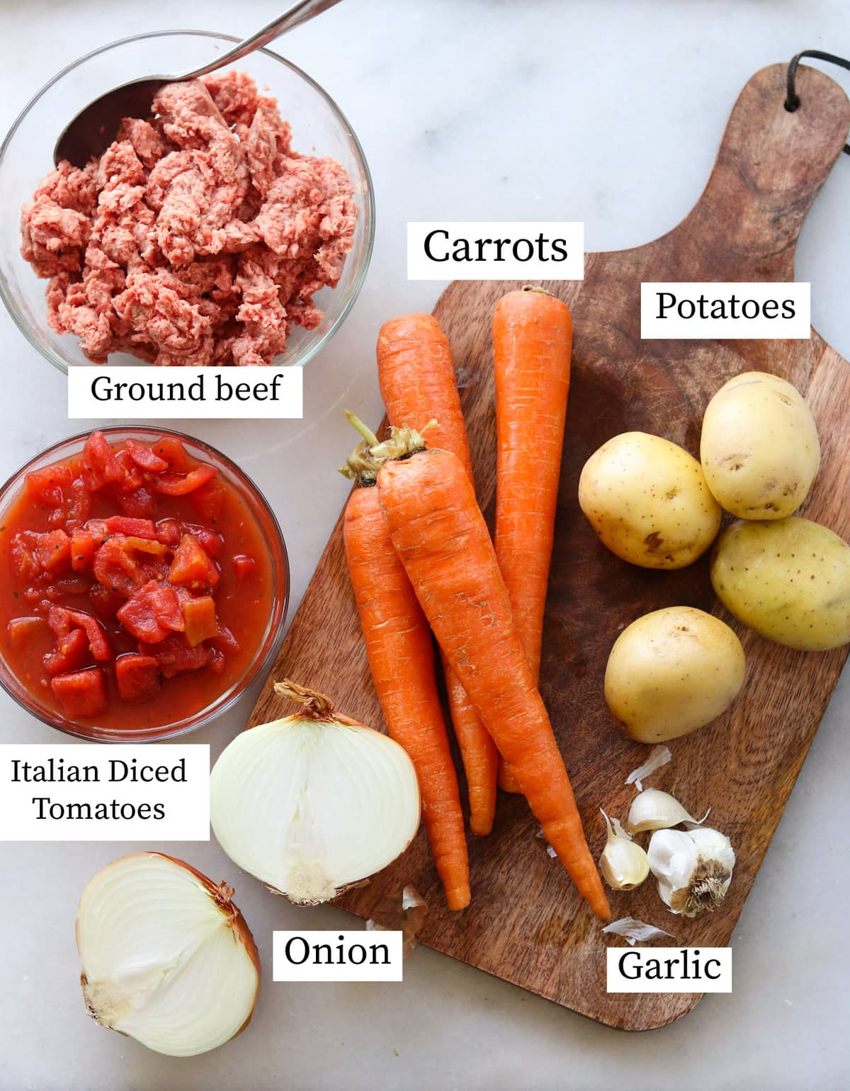 The recipe ingredients laid out on a cutting board and labeled: ground beef, carrots, potatoes, garlic, onion, and tomatoes.