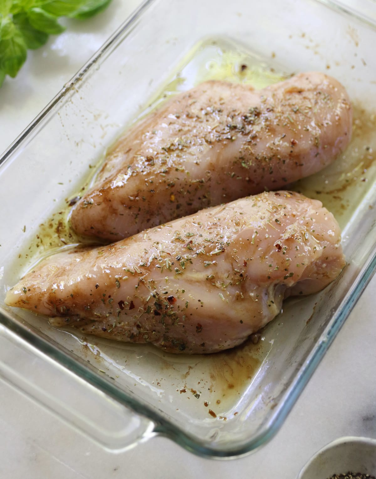 Two chicken breasts marinating in a baking dish.