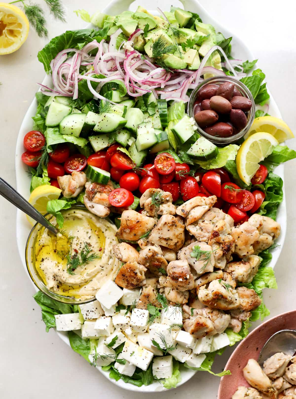 Top down of a the greek salad served on a large white platter filled with chicken and all the other toppings.