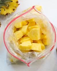 Top down off frozen pineapple pieces inside a zip top bag.