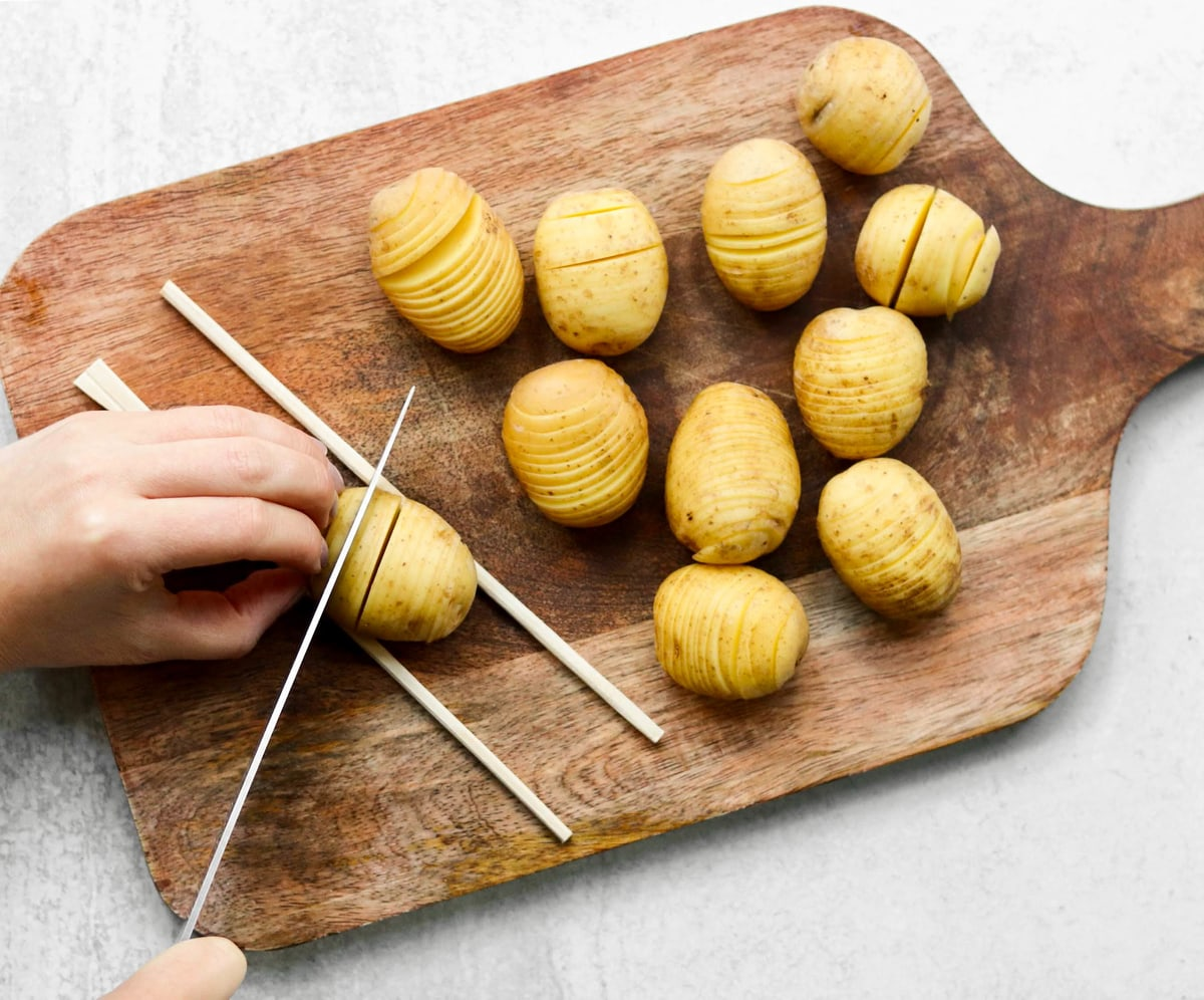Two hands slicing a mini potato set on a cutting board between two chop sticks.