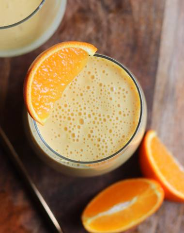 An orange smoothie in a large glass garnished with a slice of orange.
