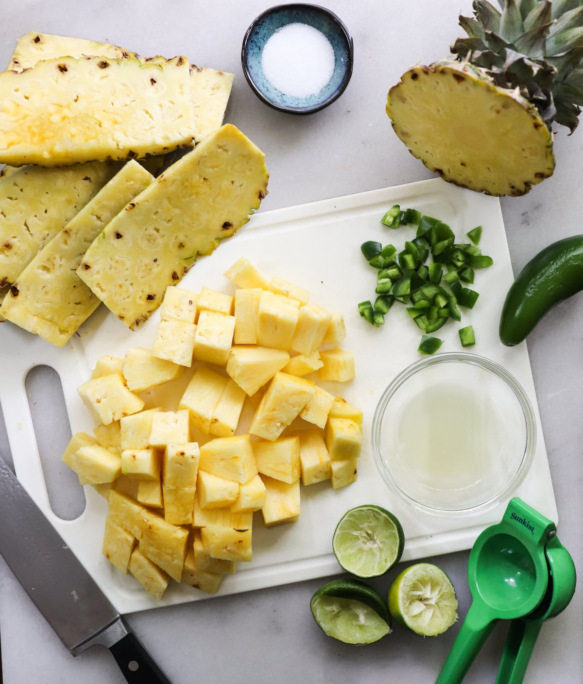 A cutting board with diced pineapple and jalapeno and juiced limes.