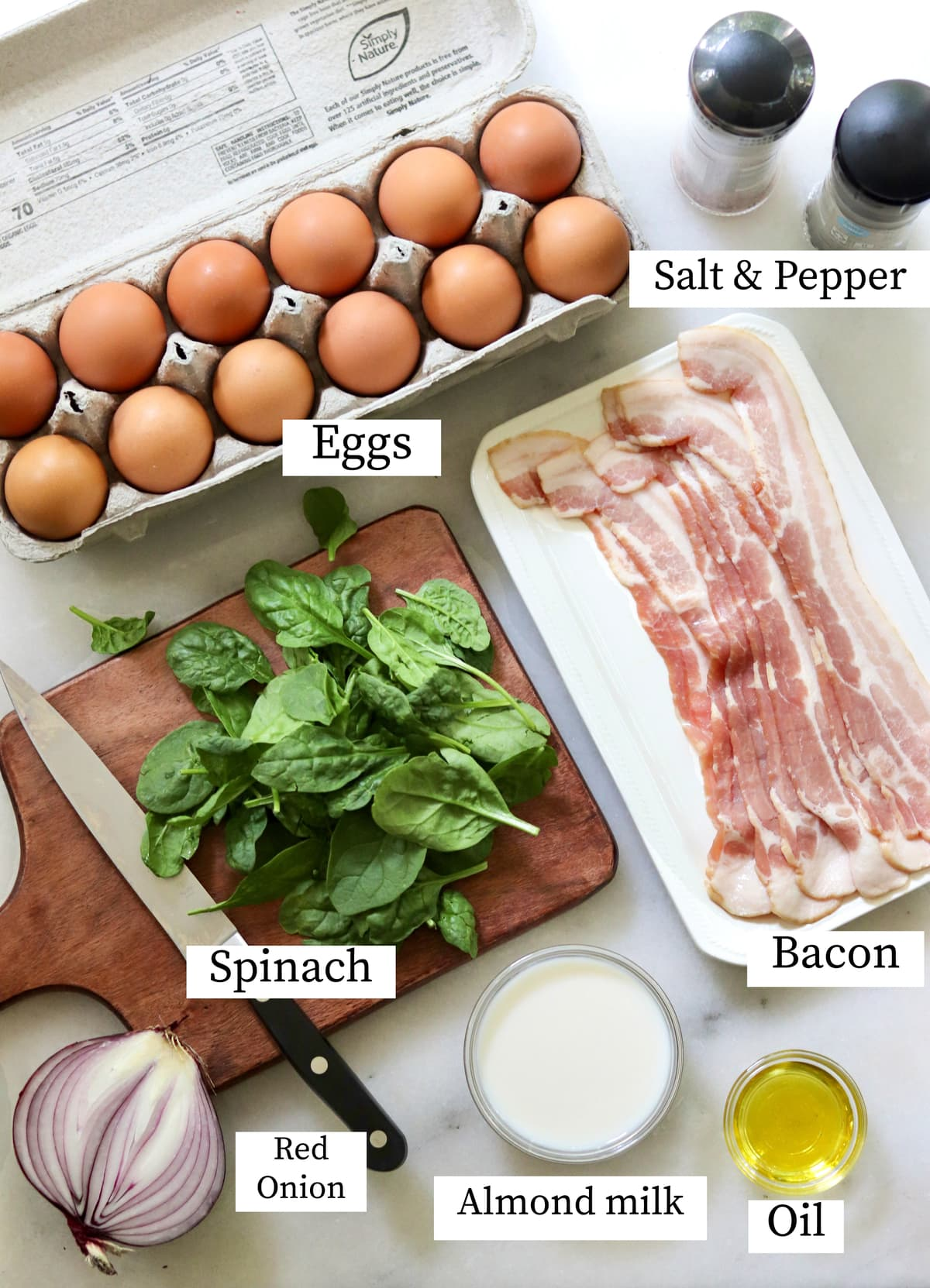 All of the recipe ingredients laid out separately and labeled: Eggs, spinach, bacon, onion, almond milk, oil, and salt and pepper.