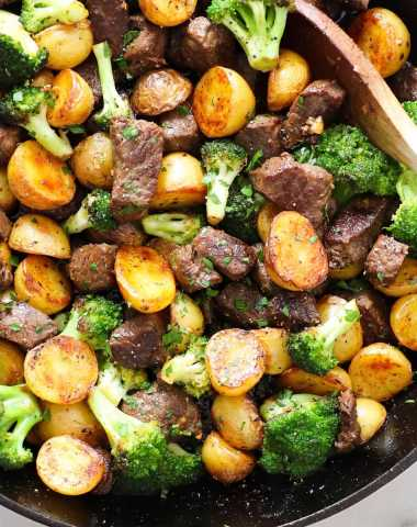 Close up of the cooked garlic butter steak bites in a cast iron skillet with potatoes and broccoli.