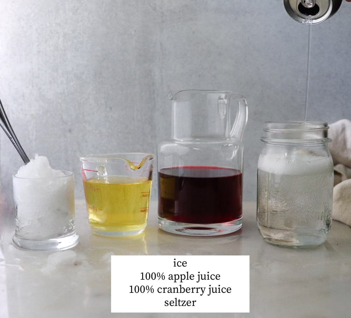 All the ingredients needed: Ice, apple juice, cranberry juice, and seltzer, each in individual glasses and labeled.