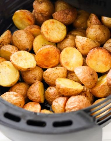 Close up of cooked baby potatoes in an air fryer basket.