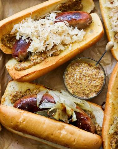 Close up of two brats in toasted rolls with sauerkraut and onions.