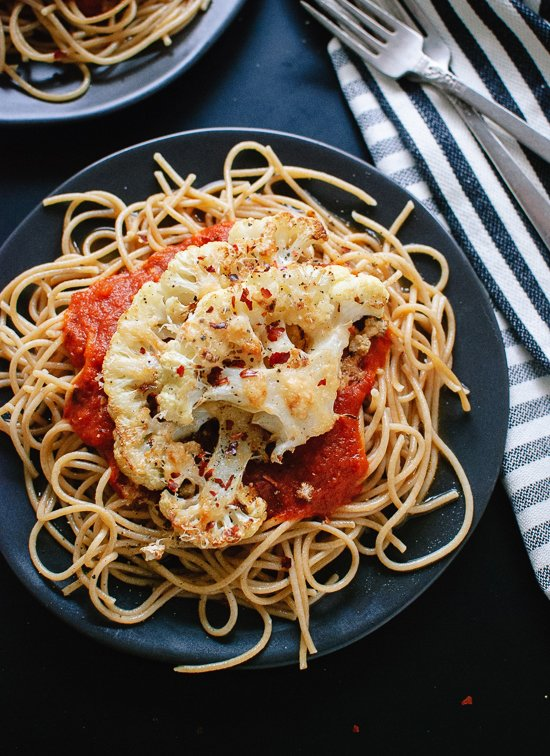 """Parmesan crusted, roasted cauliflower """"steak"""" on spaghetti with marinara. This is a super simple, healthy weeknight dinner! cookieandkate.com"""