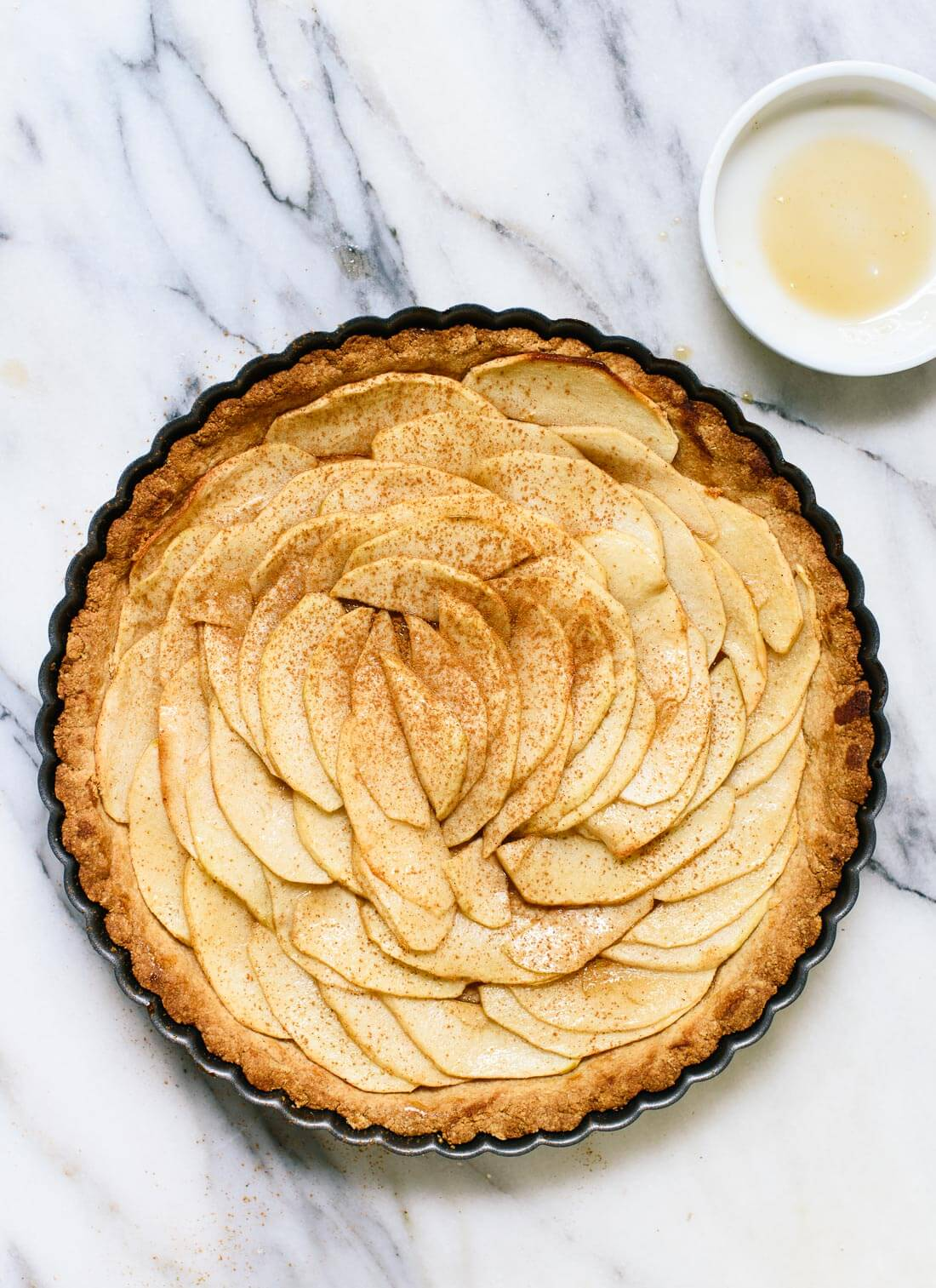 This delicious apple tart features an easy crust made with almond and oat flour. It's gluten free and easily made vegan/dairy free, too! cookieandkate.com