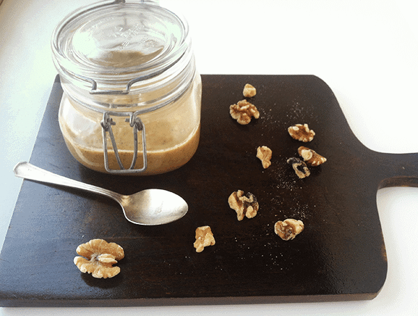 a pint size canning jar of homemade Walnut Butter on a wooden serving board next to fresh walnuts