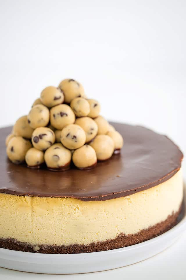 side of cheesecake on white plate showing the cheesecake, ganache, and cookie dough balls