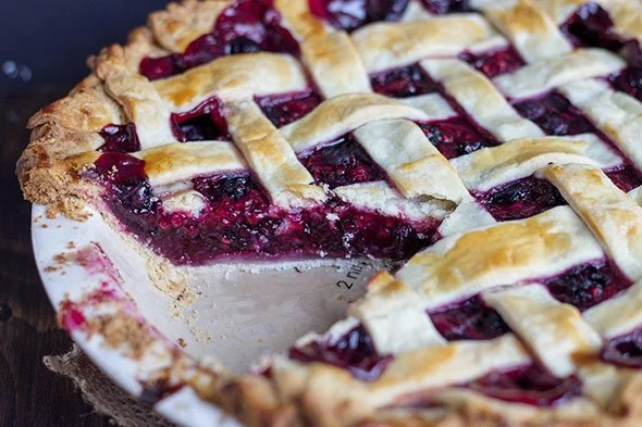 close up image of a Mixed Berry Pie with a slice removed