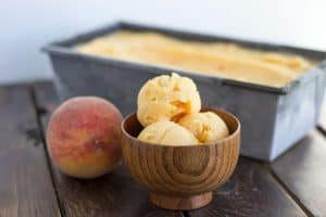 wooden ice cream bowl holding 3 scoops of Peach Sorbet
