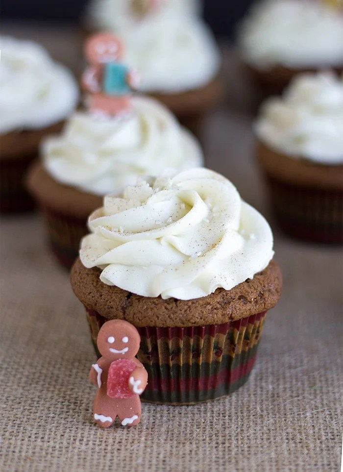 close up of gingerbread cupcakes with a fondant gingerbread cupcake topper sitting next to it