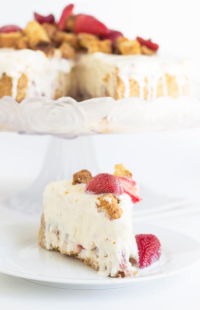 Strawberry Shortcake Cheesecake on a cake stand with a slice of it on a small plate in front of it