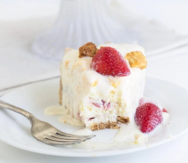 Strawberry Shortcake Cheesecake topped with vanilla frozen custard. A bite of cheesecake is missing