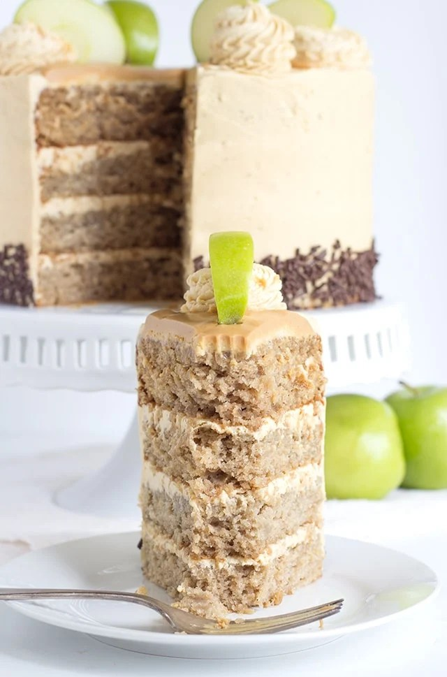a slice of 4 layer apple cake filled and topped with peanut butter frosting