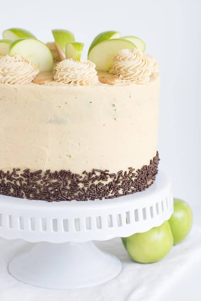 Apple Cake with Peanut Butter Frosting and chocolate jimmies on a white cake stand
