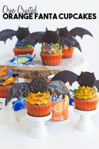 OREO Crusted Orange Fanta Cupcakes - Adorable bat topped orange flavored cupcakes with a cute swirl of Halloween colored frosting! The cupcakes are also dipped in a orange Fanta glaze and crusted with OREO cookies for an extra touch.