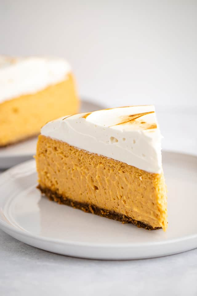 slice of sweet potato cheesecake on white plate with a slice of cheesecake behind it