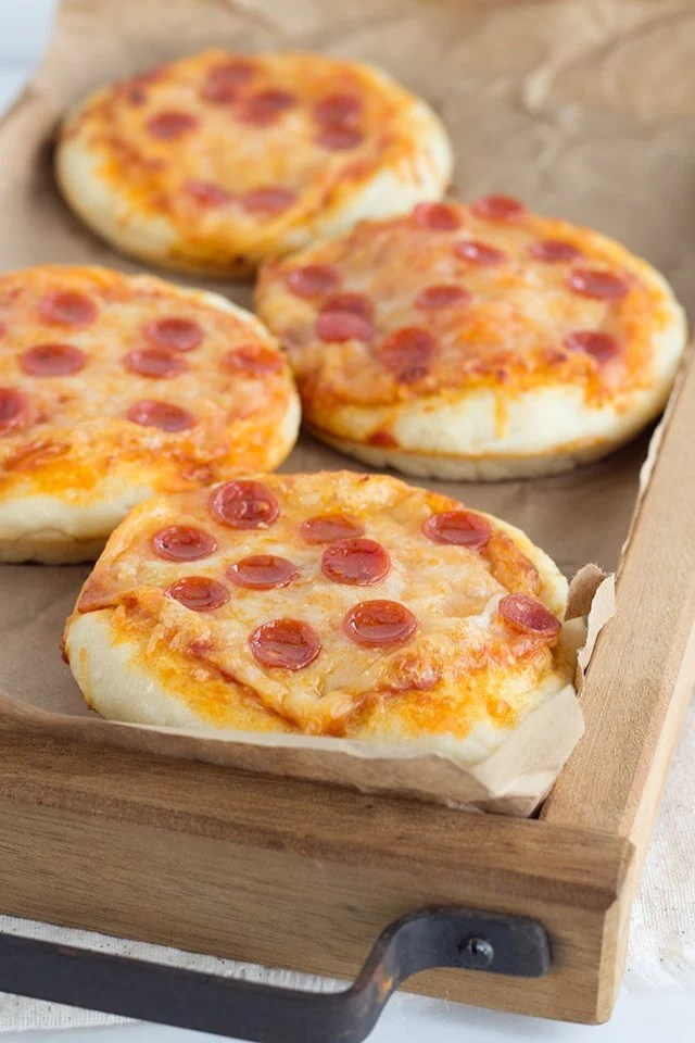 Mini Pizzas topped with pepperoni on a wooden serving tray