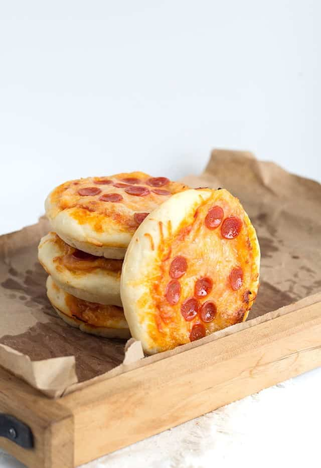 Wooden serving tray holding Mini Pizzas topped with bite sized pepperoni and cheese