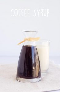 carafe of homemade coffee syrup with a glass of milk behind it