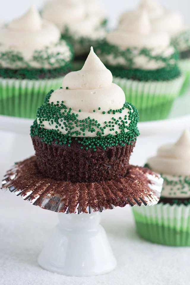 One Chocolate Guinness Cupcake with Baileys Cream Cheese Frosting and green nonpariels with the cupcake liner partially unwrapped from around the cupcake