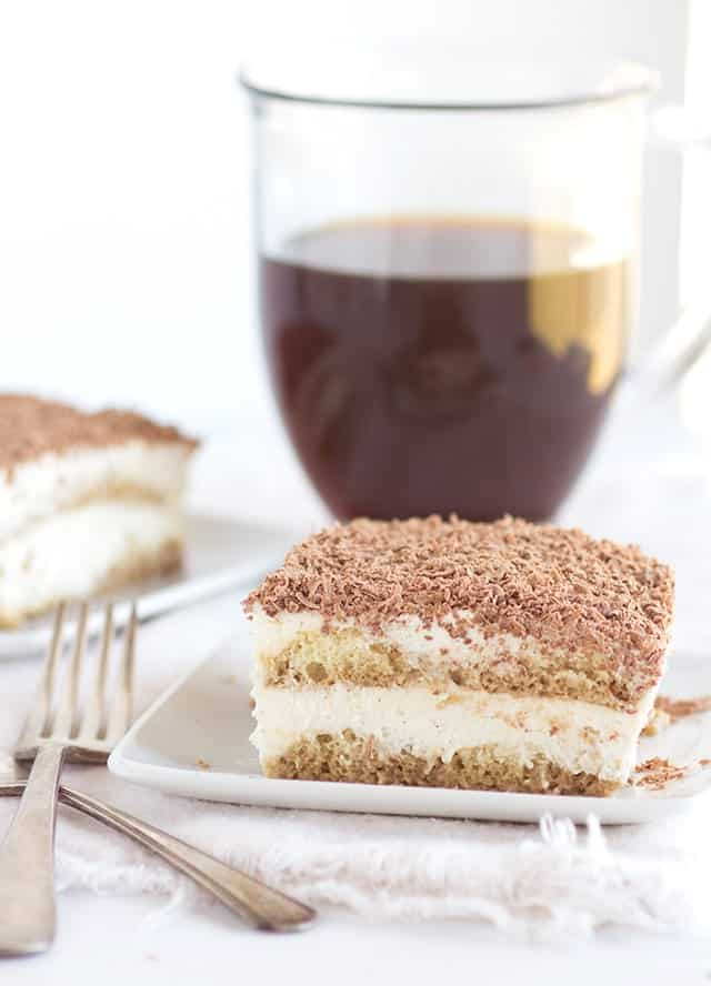 Plate of Tiramisu next to a mug of coffee