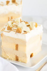 No Bake White Chocolate Peanut Butter Dessert - layers of buttery pound cake, peanut butter mousse, white chocolate ganache and topped with white chocolate peanut butter cups! This is the perfect summer treat!