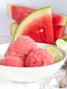 3 scoops of Watermelon Sorbet in a bowl next to slices of fresh watermelon