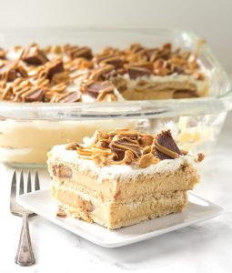 Peanut Butter Ice Box Cake - layers of graham crackers, peanut butter cream cheese stuffed with peanut butter cups, and whipped cream