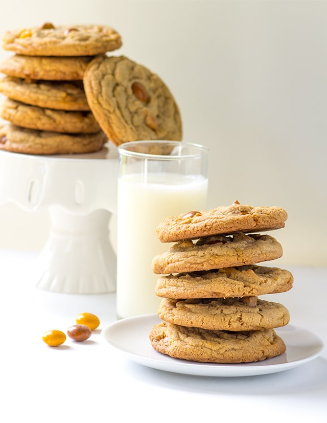 a white plate stacked high with butterscotch M&M cookies next to a glass of milk
