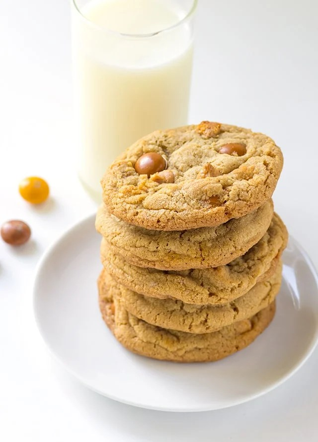 a plate with a stack of chewy homemade cookies loaded with butterscotch chips and butterscotch m&ms.