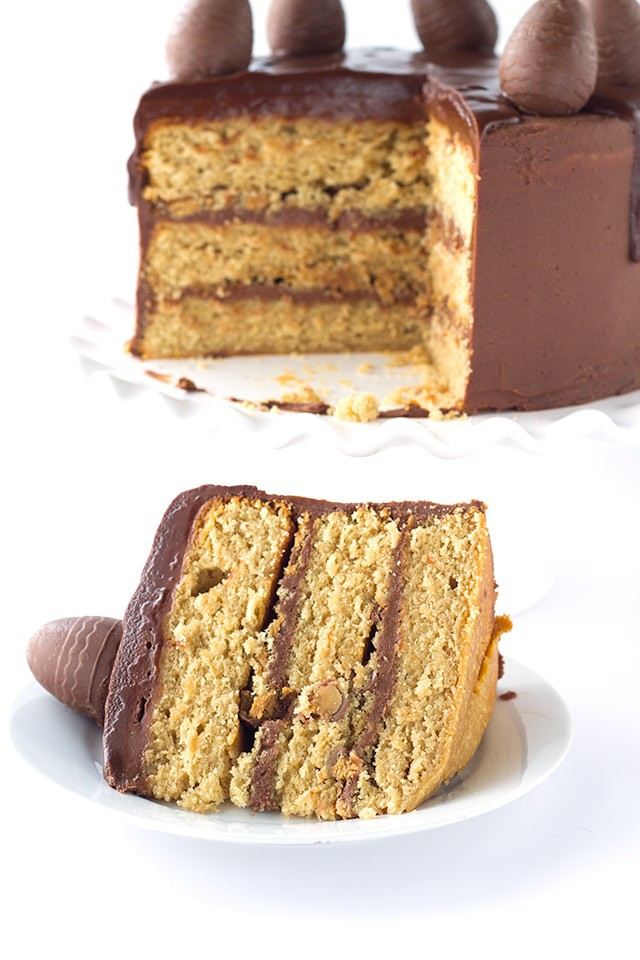 Peanut Butter Cake with Chocolate Frosting - peanut butter cake filled with chocolate frosting and chopped peanut butter cups. Top this cake with a chocolate peanut butter ganache and cute peanut butter filled chocolate eggs for EASTER!